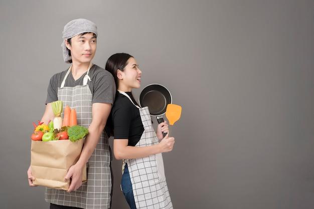 幸せなカップルは食料品の袋の灰色の壁に野菜を持っています。