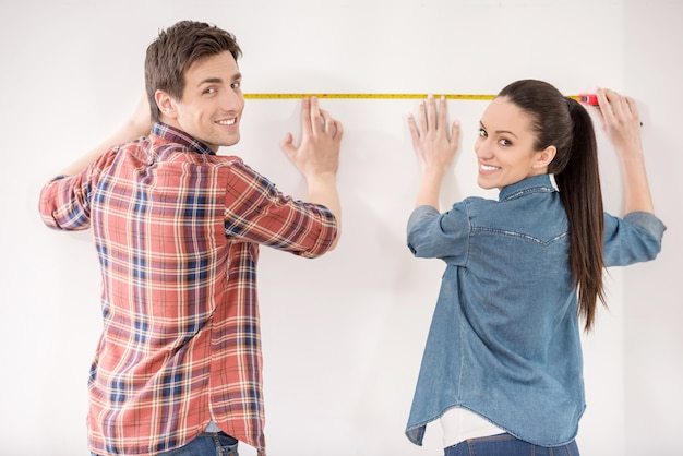 Happy couple is measuring their new empty apartment.