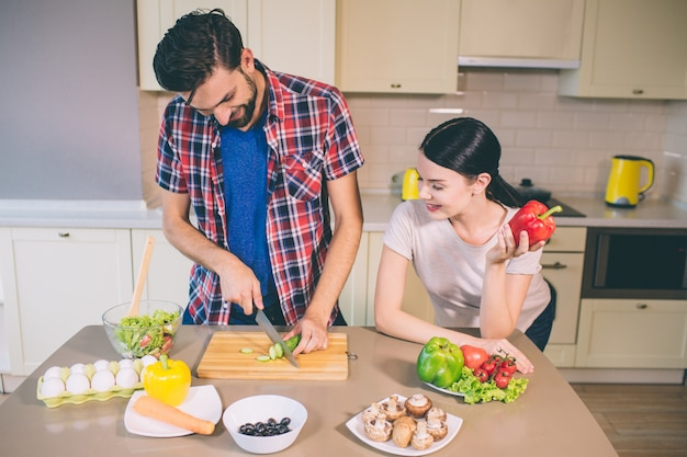 Happy couple is staying together. he cuts cucumber into pieces.