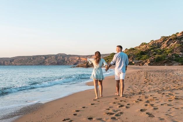 幸せなカップルは、日没または日の出の間にビーチを歩いています。
