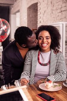 幸せなカップル。彼女にキスをしながら彼のガールフレンドの近くに立っているうれしそうな素敵な男