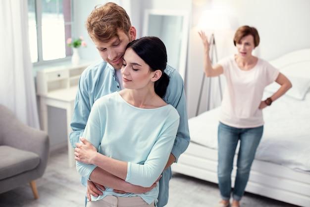 幸せなカップル。彼女を抱きしめながら彼の妻の後ろに立っているうれしそうな前向きな男