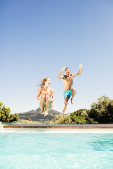 Happy couple jumping in the pool in a sunny day