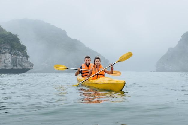 하롱 베이의 안개 낀 바다에서 행복한 커플 카약. 석회암 섬이 있는 얼굴에서 보기