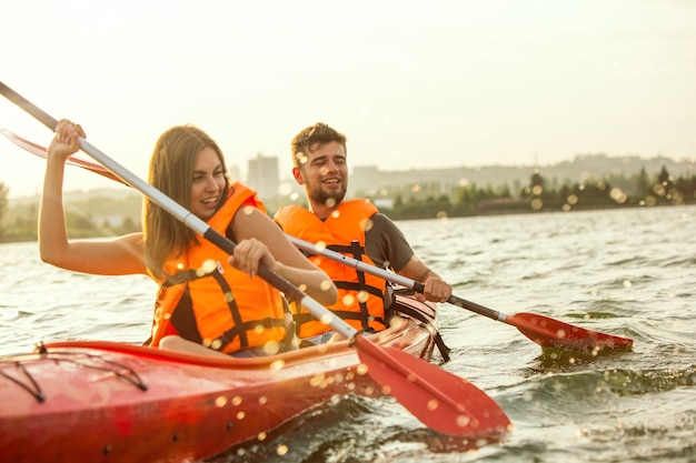 Happy couple kayaking on river with sunset on the background