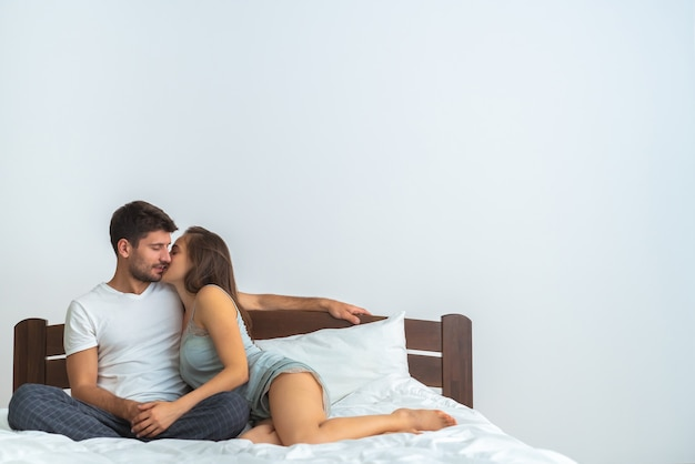 The happy couple kissing on the bed on the white background