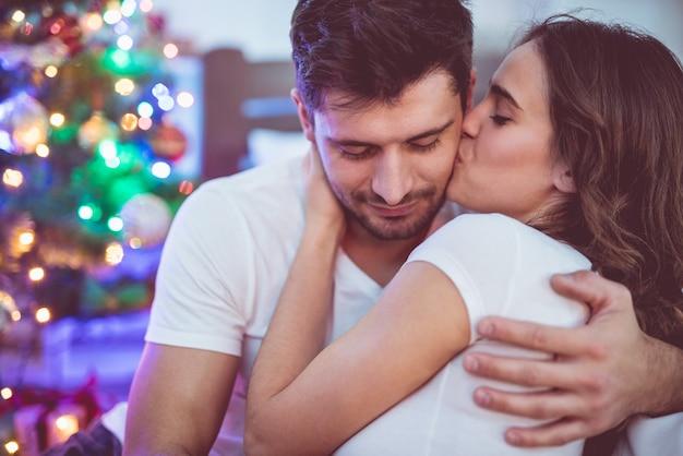 The happy couple kissing near the christmas tree