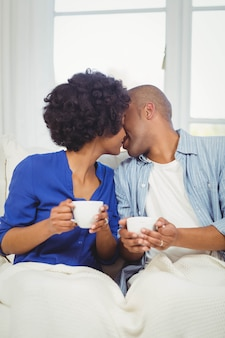 Happy couple kissing on the sofa while holding cups