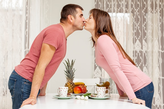 Happy couple kissing over a table