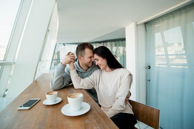 Счастливая пара смеется и держится за руки, глядя друг на друга. большой белый зал с панорамными окнами. молодой мужчина и женщина на свидании в кафе. пустые чашки на столе.