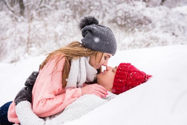 幸せなカップルが横たわり、雪の中でキス