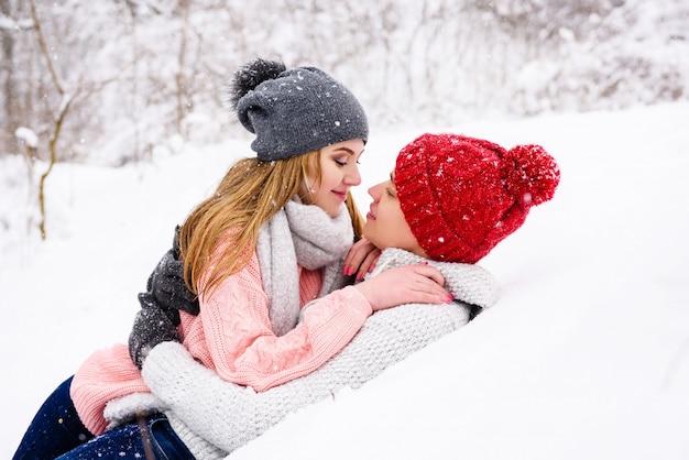 幸せなカップルが雪の中で横たわった