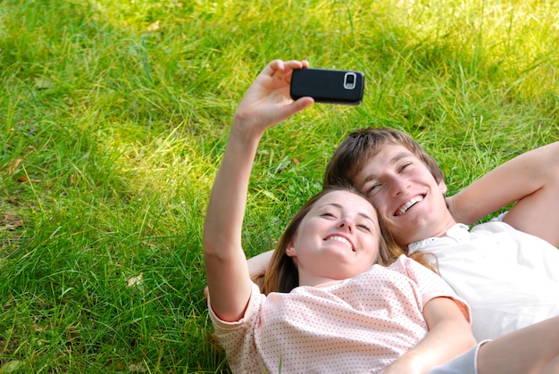 Happy couple laying on grass make self-photo
