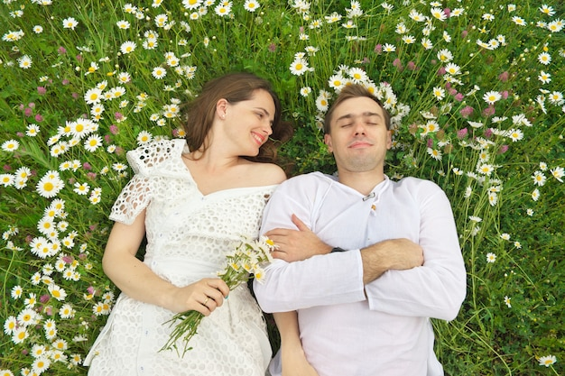 Happy couple lie in a camomile flower.