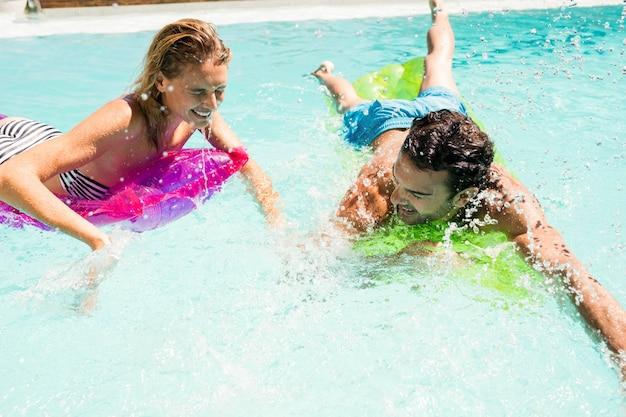 Happy couple on lilos splashing in the pool