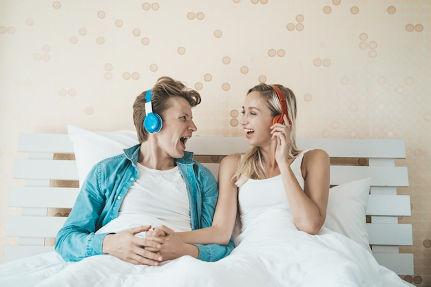 Happy couple listening song in the morning at bedroom