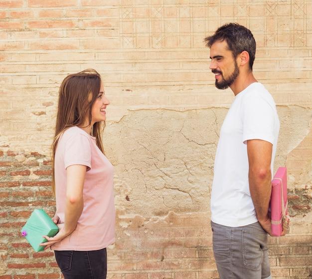 Счастливая пара, глядя друг на друга, скрывая подарок за спиной