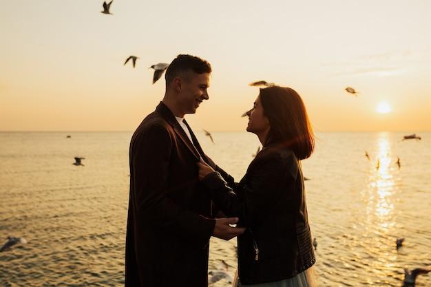 表面に飛んでいるカモメと一緒にビーチで休日にお互いを見ている幸せなカップル。