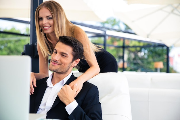 レストランでノートパソコンを見て幸せなカップル