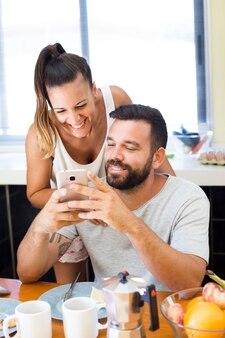 朝食、携帯電話の画面を見て幸せなカップル