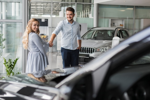 Happy couple looking at a car