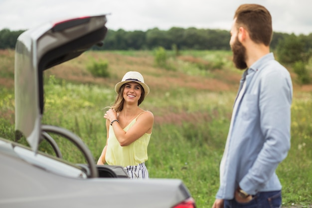 Happy couple looking at each other standing near the car with open trunk