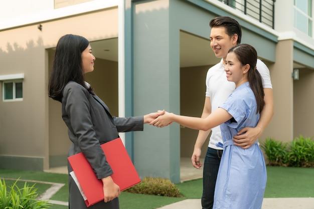 Счастливая пара ищет свой новый дом и обменивается рукопожатием с брокером по недвижимости после сделки