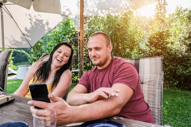 スマートフォンの家の庭のバーベキューディナーを探している幸せなカップル
