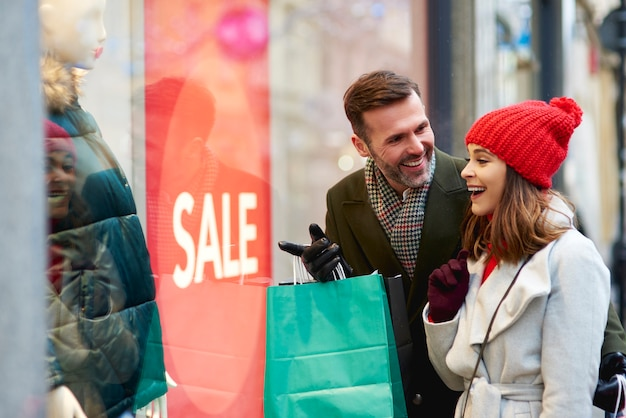 Happy couple looking at shop window with clothing