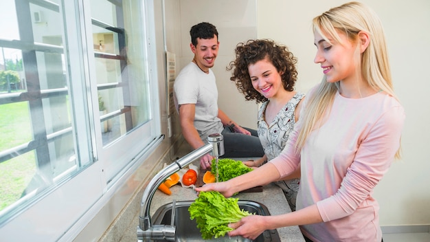 Happy couple looking at young female friend washing the lettuce in the kitchen sink
