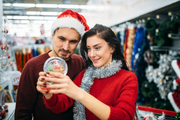 행복 한 커플 슈퍼마켓, 가족 전통에서에서 크리스마스 스노우 글로브에 보인다. 12 월 명절 상품 및 장식 쇼핑