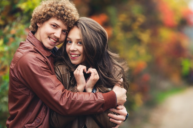 Happy couple in love in autumn curly-haired mustachioed man and ruddy-haired woman in leather jackets and jeans
