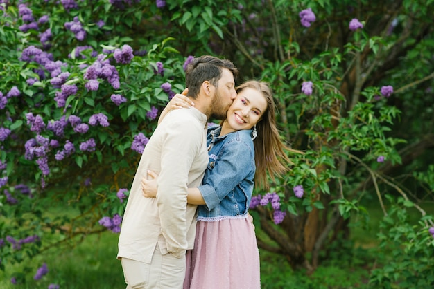Happy couple in love in blooming lilac gardens in spring.