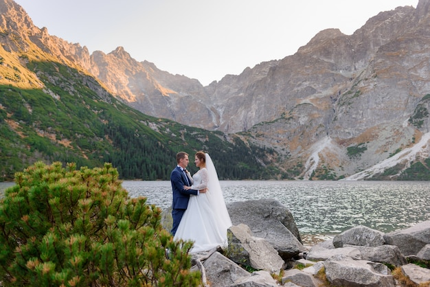 Happy couple in love dressed in wedding outfits is almost kissing with breathtaking view of mountains and highland lake