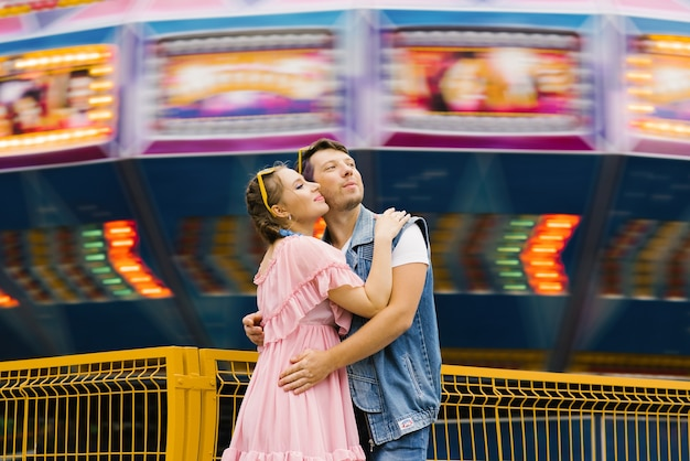 Happy couple in love enjoying each other in an amusement park