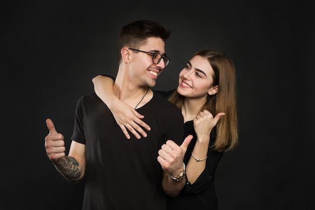 행복 한 커플 사랑 흥분 미소 지주 엄지 손가락 제스처, 아름 다운 젊은 남자와 여자는 검은 배경 위에 절연 카메라를보고 미소