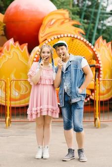 Happy couple in love having fun in an amusement park, eating lollipops