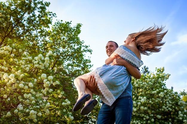 Happy couple in love having fun in blooming garden