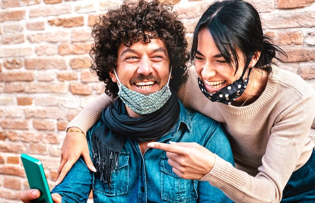 Happy couple in love having fun with mobile smart phone wearing face mask