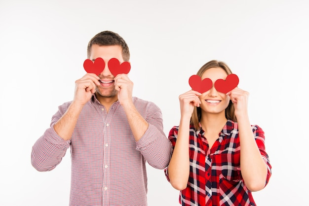 Happy couple in love hiding eyes behind paper hearts