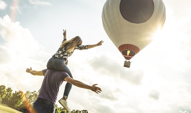 Happy couple in love on honeymoon vacation cheering at hot air balloon