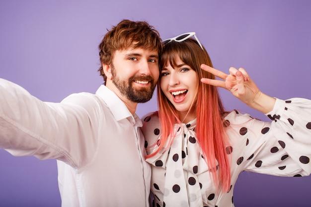 Happy couple in love making self portrait on purple wall