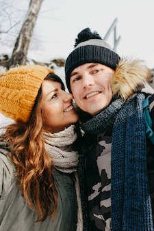 Happy couple in love making selfie at forest nature park in cold season.