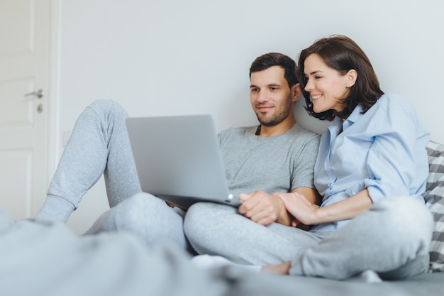 Happy couple in love review their wedding photos on laptop computer