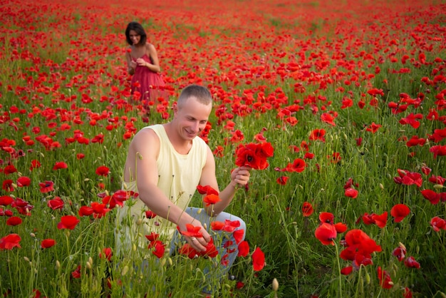 Happy couple in love tenderness on poppy spring field. well being boyfriend girlfriend family, country nature.