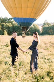 Happy couple in love walking together in beautiful summer field, holding hands and ready to have wonderful travel on hot air balloon