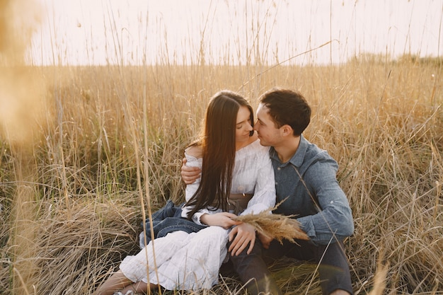Happy couple in love in wheat field at sunset