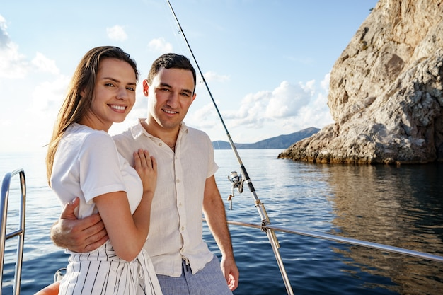 Happy couple in love on a yacht in summer on romantic vacation