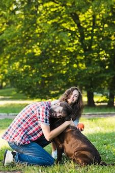 Happy couple loving their dog in garden