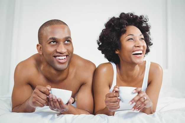 Happy couple lying on bed while holding cups and looking up